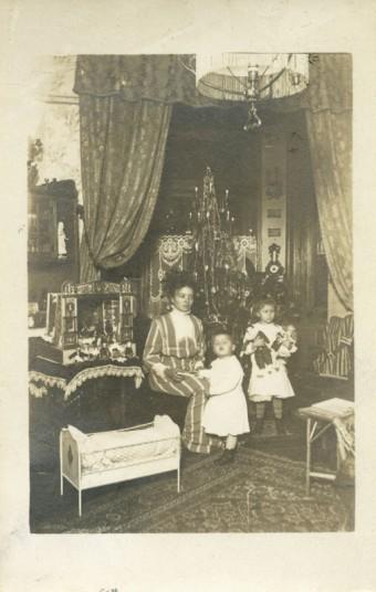 Matka s dvěma malými dětmi u vánočního stromku, repr. fotopohlednice, 1909, Zdroj: archiv MMP